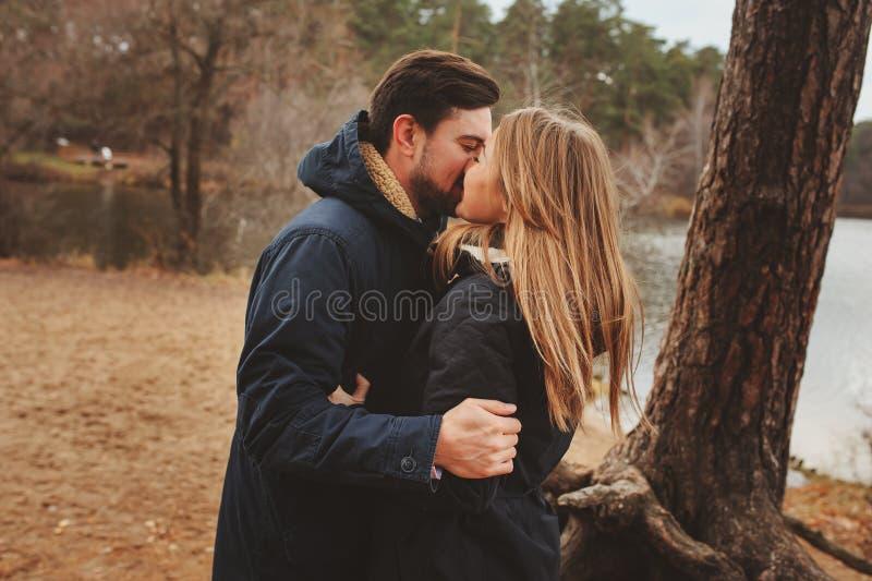 Het houden van jonge paar gelukkige samen openlucht op comfortabele warme gang in de herfstbos stock foto's