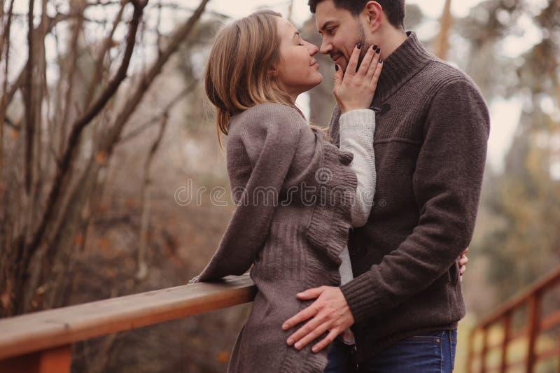 Het houden van jonge paar gelukkige samen openlucht op comfortabele warme gang in de herfstbos royalty-vrije stock afbeelding