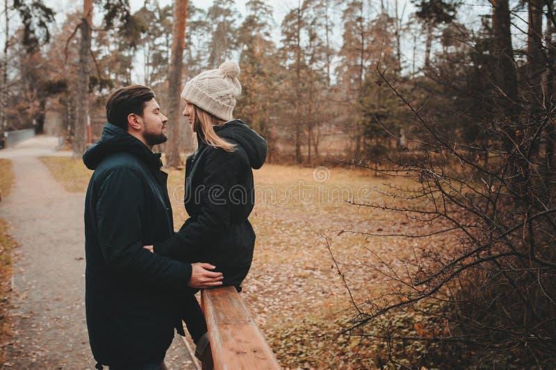 Het houden van jonge paar gelukkige samen openlucht op comfortabele warme gang in de herfstbos stock fotografie