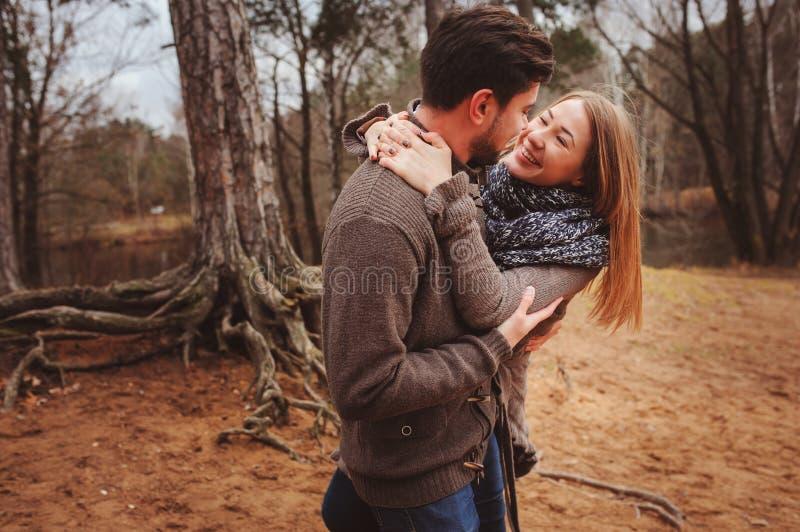 Het houden van jonge paar gelukkige samen openlucht op comfortabele warme gang in de herfstbos royalty-vrije stock foto