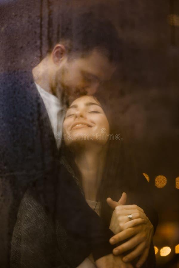Het houden van van kerel koestert en kust zijn gelukkig meisje die zich achter een nat venster met lichten bevinden Romantisch pa royalty-vrije stock foto