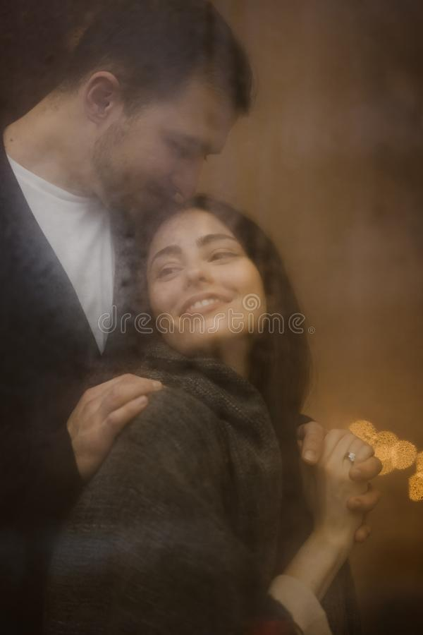 Het houden van van kerel koestert en kust zijn gelukkig meisje die zich achter een nat venster met lichten bevinden Romantisch pa stock foto
