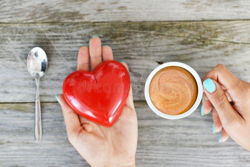 Het houden van koffieconcept met handen van een vrouw die één rood hart en één kop van espressokoffie houden op houten achtergron stock foto's