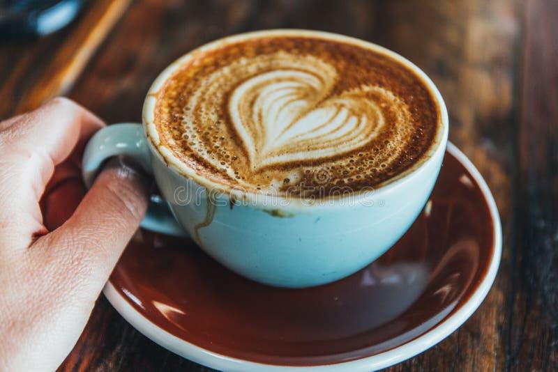 Het houden van a-kop van koffie op houten lijst stock fotografie