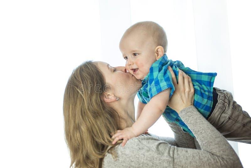 Het houden van moeder het spelen met haar baby dicht bij een venster royalty-vrije stock afbeelding