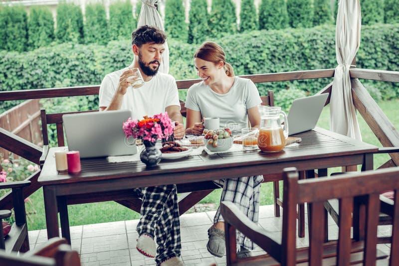 Het houden van ontbijt hebben en van echtgenoten die toont in openlucht op laptop letten op royalty-vrije stock afbeeldingen