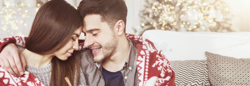 Het houden van paar het drinken van over*wegen-wijn tegen Kerstmisboom stock fotografie
