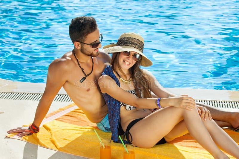 Het houden van paar het ontspannen in de zon bij de pool royalty-vrije stock fotografie