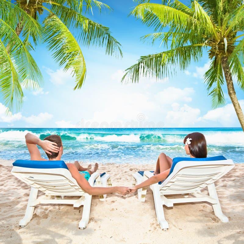 Het houden van paar het ontspannen op het strand royalty-vrije stock afbeeldingen
