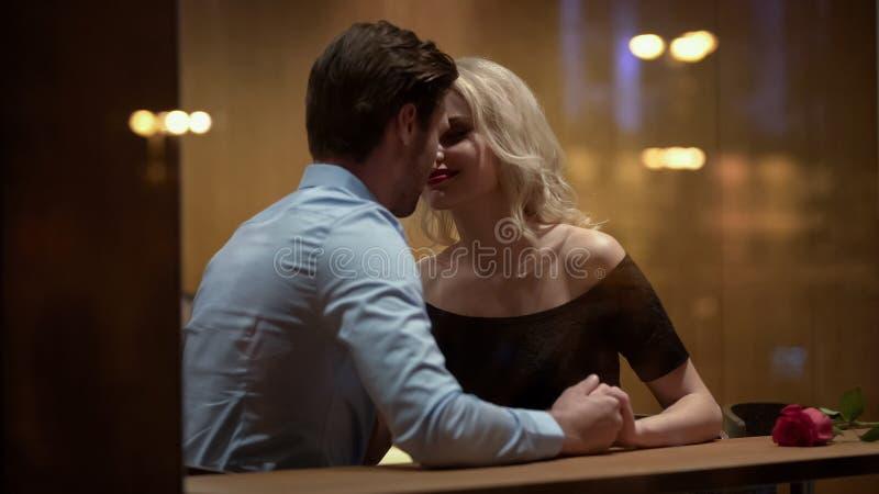 Het houden van paar het kussen in restaurant, die van elkaar, romantische datum, hartstocht genieten royalty-vrije stock afbeeldingen