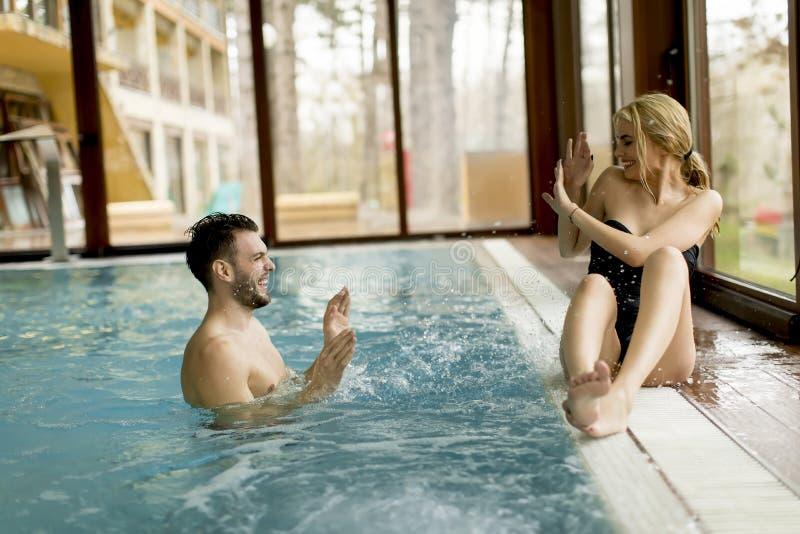 Het houden van paar het ontspannen in het kuuroord door de pool stock fotografie