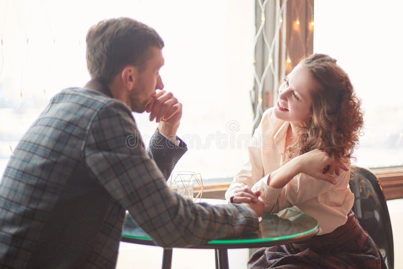Het houden van paar spreken, die dichtbij het venster in een comfortabele koffie zitten stock fotografie