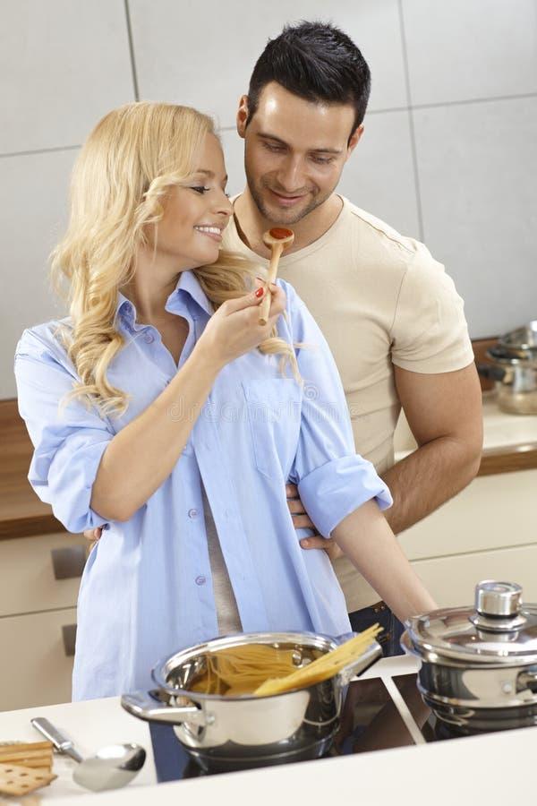 Het houden van paar van proevende saus in keuken stock fotografie