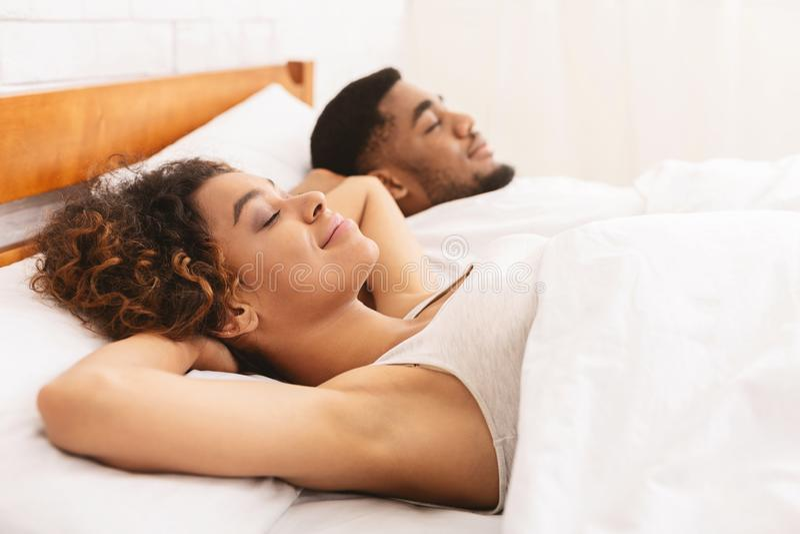 Het houden van paarslaap in bed en het koesteren stock foto's