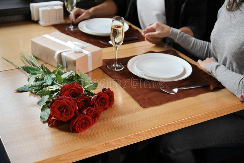 Het houden van paarzitting bij lijst in restaurant op romantische datum stock afbeeldingen