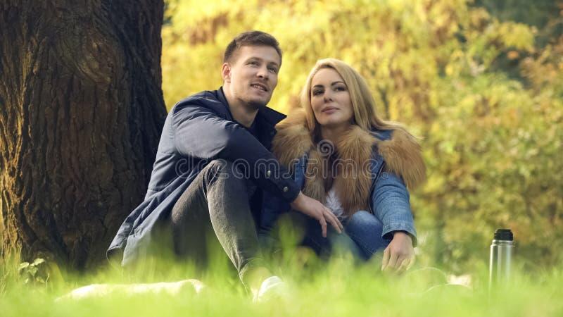 Het houden van paarzitting onder boom, die datum hebben in openlucht, picknick in parkgeluk royalty-vrije stock afbeelding
