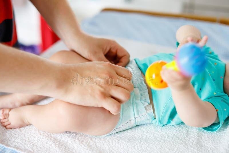 Het houden van vader van veranderende luier van zijn pasgeboren babydochter Weinig kind, meisje op veranderende lijst in badkamer stock afbeelding