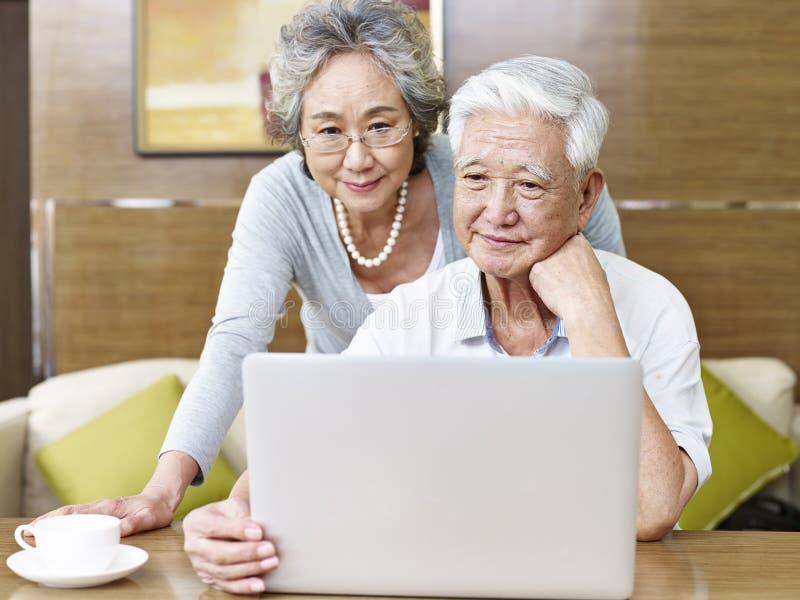 Het houden van van hoger Aziatisch paar die laptop met behulp van royalty-vrije stock foto's