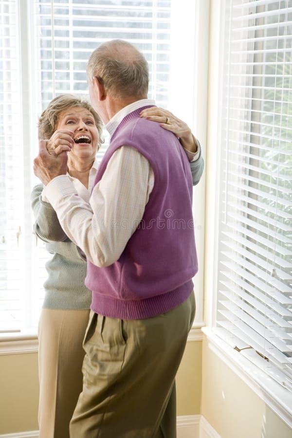 Het houden van van hoger paar dat in woonkamer danst royalty-vrije stock foto
