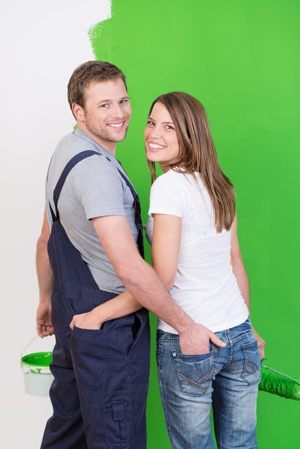 Het houden van van jong paar die hun nieuw huis schilderen stock afbeelding