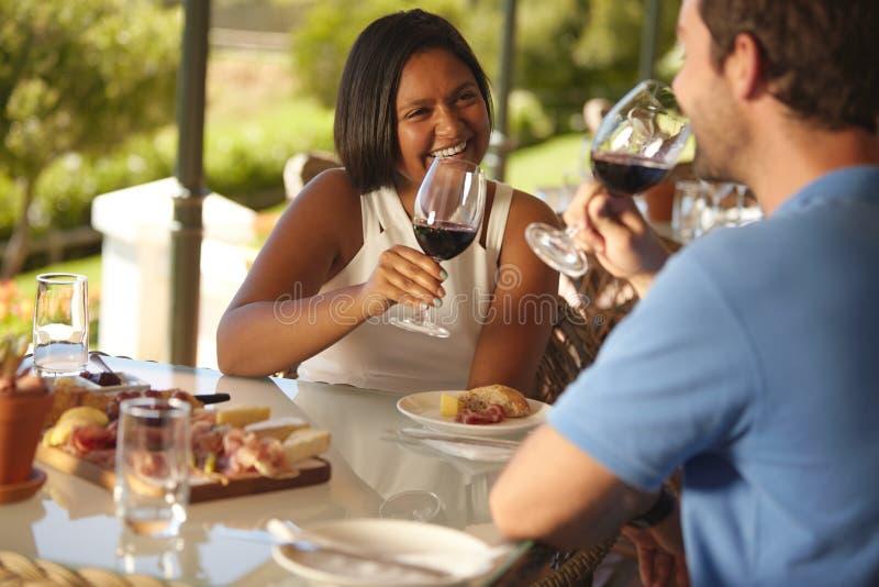 Het houden van van jong paar die rode wijn drinken bij wijnmakerij stock afbeeldingen
