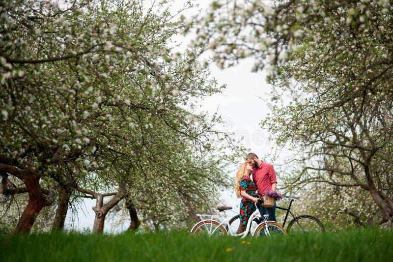 Het houden van van jong paar met fietsen in de lentetuin stock afbeeldingen
