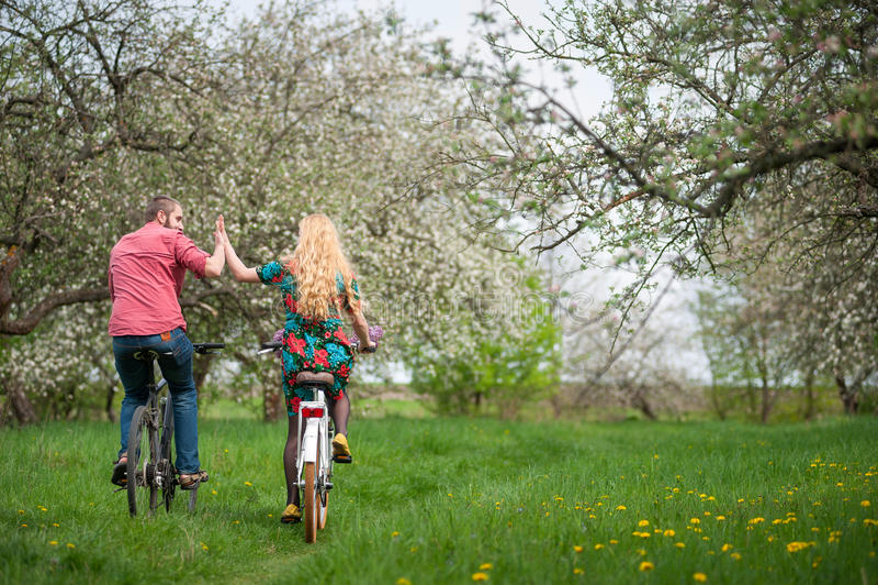 Het houden van van jonge paar berijdende fietsen in de de lentetuin stock afbeeldingen