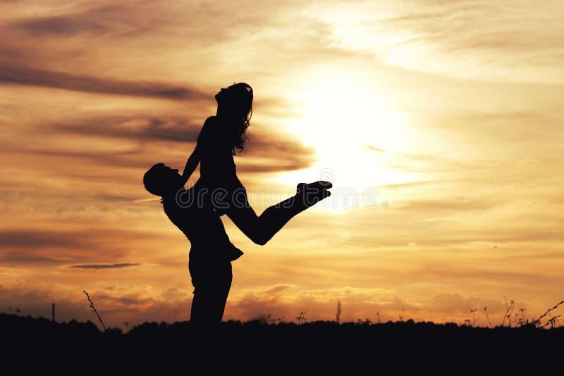 Het houden van van mooi paar van kerels en meisjes bij zonsondergang op gebied stock fotografie