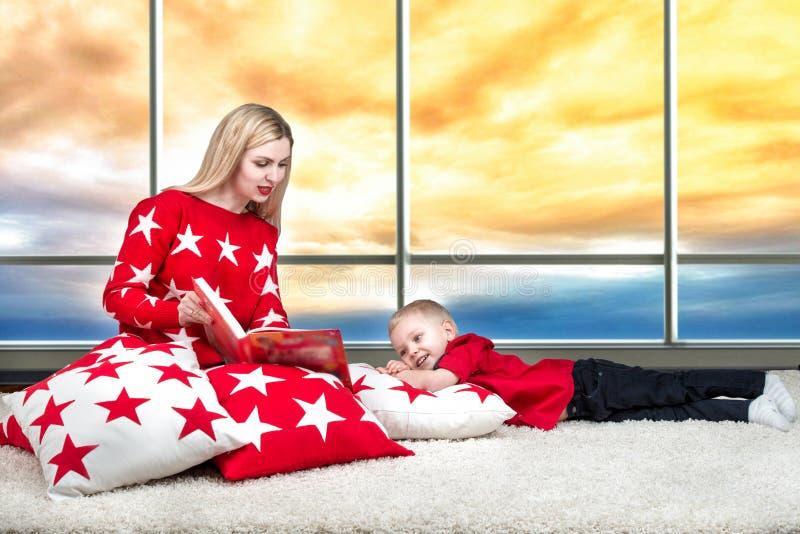 Het houden van van mooie jonge moeder leest een boek aan zijn kleine zoon Het liggen op de hoofdkussens voor binnenhuisarchitectu royalty-vrije stock foto's