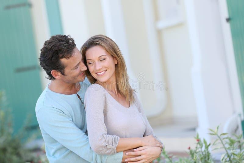 Het houden van van paar die op middelbare leeftijd vooraan hun nieuw huis omhelzen royalty-vrije stock foto's