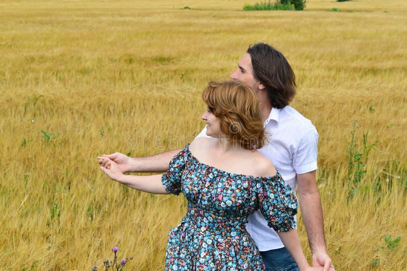 Het houden van van paar die op middelbare leeftijd zich op gebied in de zomer bevinden royalty-vrije stock foto's