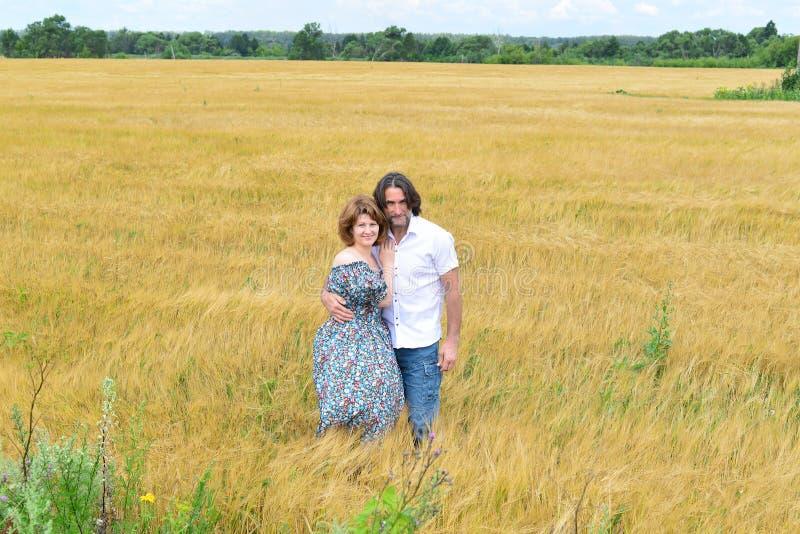 Het houden van van paar die op middelbare leeftijd zich op gebied in de zomer bevinden royalty-vrije stock afbeelding