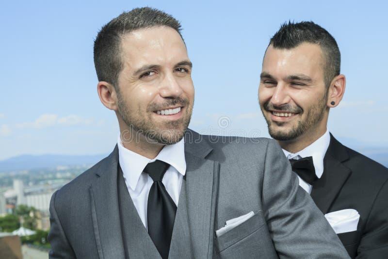 Het houden van van vrolijk mannelijk paar op hun huwelijksdag stock foto