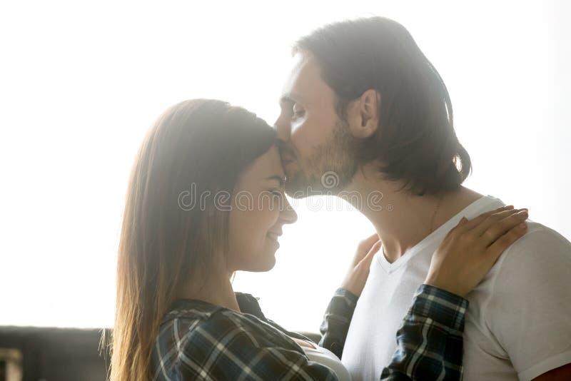 Het houden van vriend van kussend meisje die op voorhoofd intimat genieten van royalty-vrije stock afbeeldingen