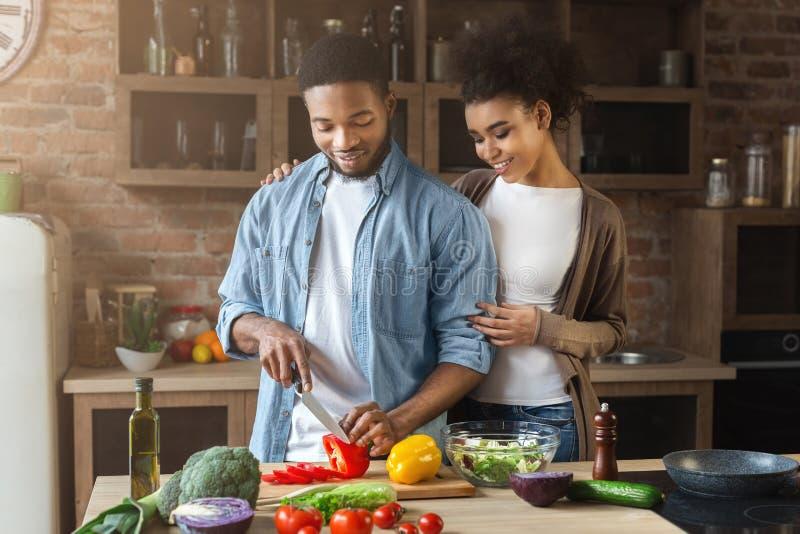 Het houden van van zwarte vrouw die echtgenoot koesteren terwijl het koken stock foto's