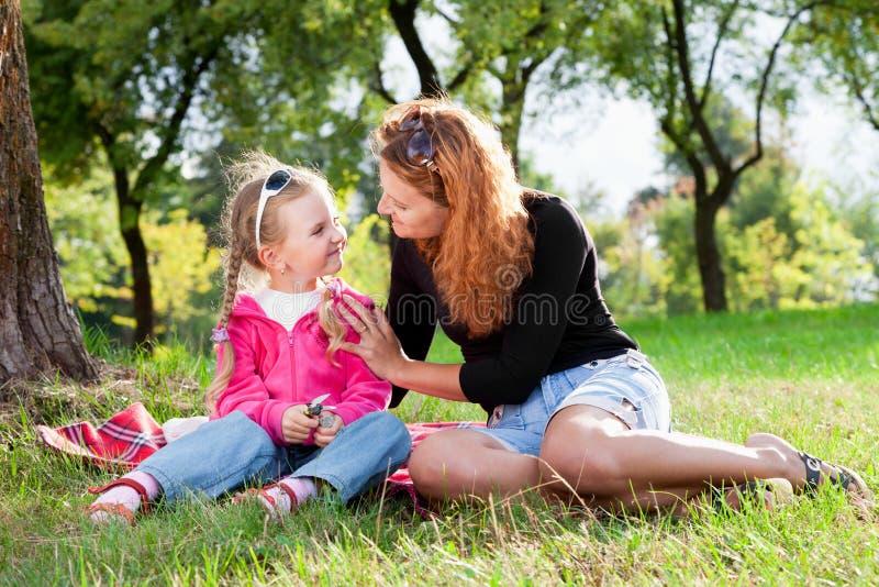 Het houdende van moeder en meisje rusten stock foto's