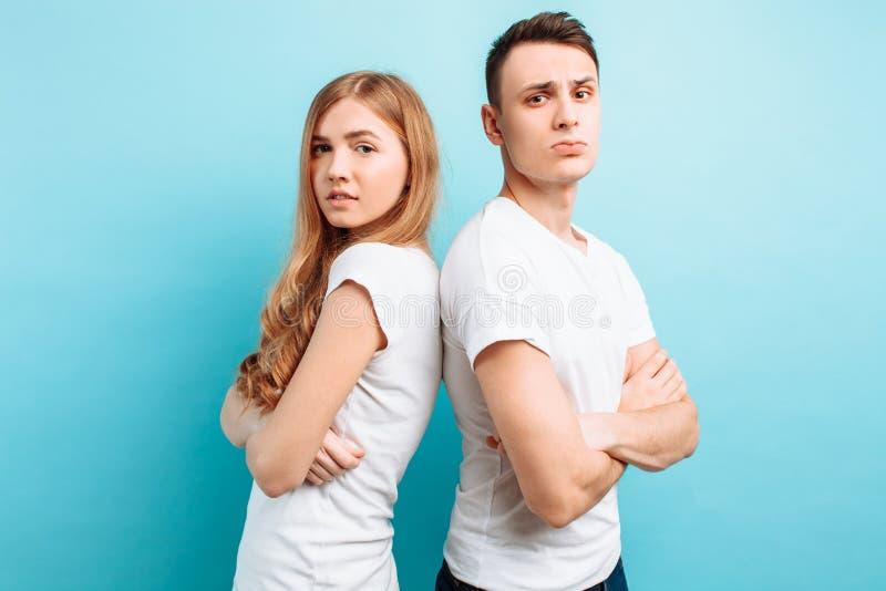 Het houdende van paar, de man en de vrouw, kleedden zich in witte T-shirts, rijtjes en glimlachend, tegen een blauwe achtergrond stock fotografie