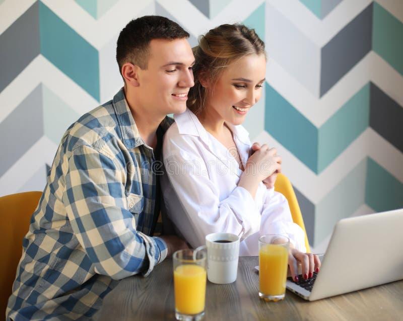 het houdende van paar die ontbijt hebben en laptop bekijken verwerkt gegevens royalty-vrije stock fotografie