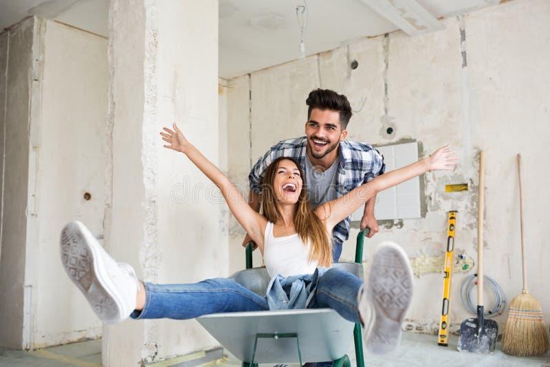 Het houdende van paar heeft pret terwijl het vernieuwen van hun huis stock afbeelding