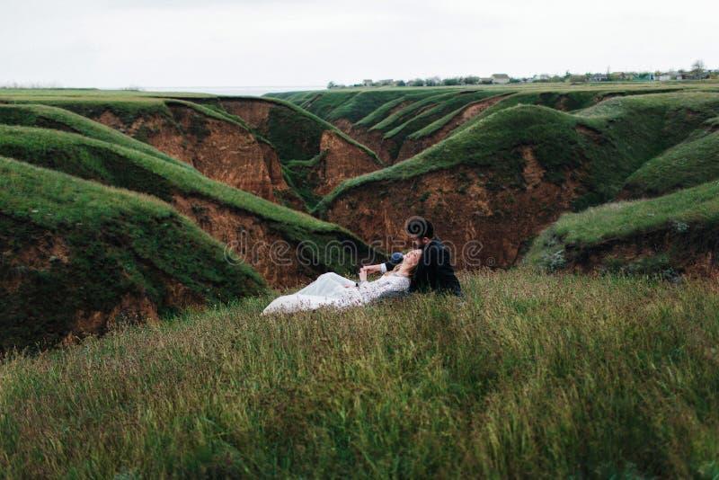 Het houdende van paar ligt op een gras stock afbeelding