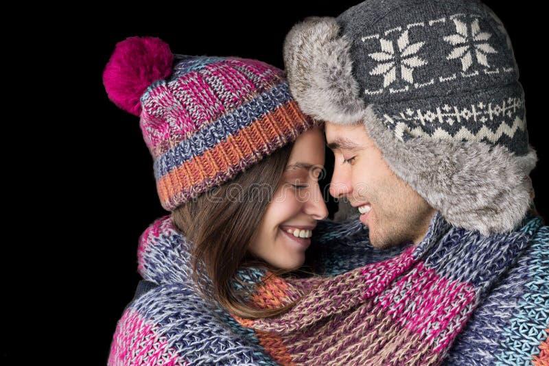 Het houdende van Paar in Warme Kleren omhelst Geïsoleerd op Zwarte Achtergrond royalty-vrije stock foto