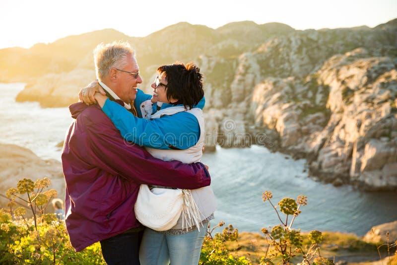 Het houdende van rijpe paar reizen, die zich op de bovenkant van rots, het onderzoeken bevinden royalty-vrije stock foto