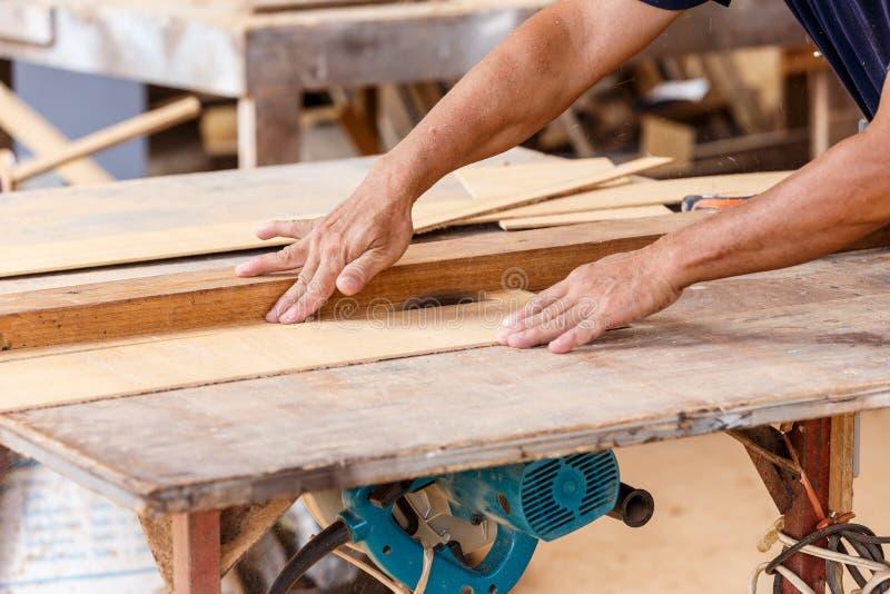 Het hout van de de zaagbesnoeiing van het timmermansgebruik voor maakt nieuw meubilair royalty-vrije stock foto's