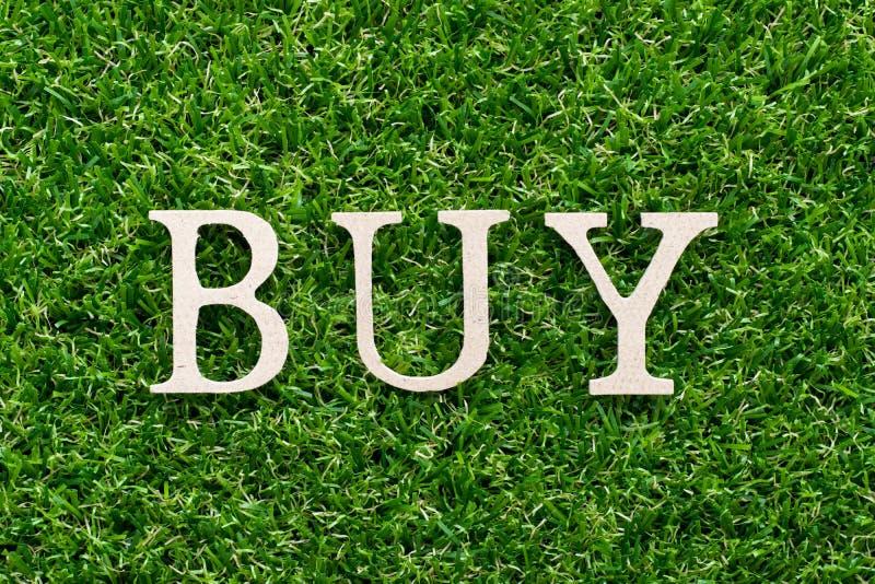 Het houten alfabet in woord koopt op groene grasachtergrond stock fotografie