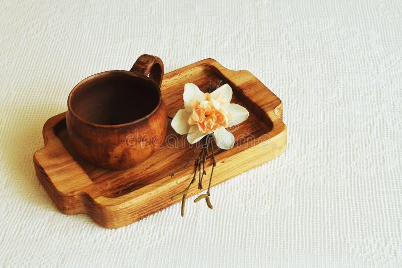 Het houten beukdienblad met originele kleikop en berk vertakt zich met gevoelige witte narcissen op helder kantservet Concept voo stock foto