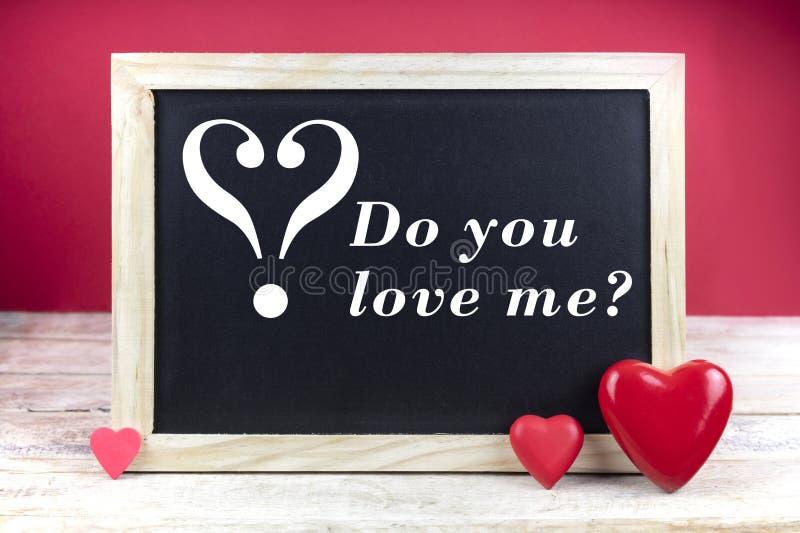 Het houten bord met rode harten en de tekst u houden van me? op rode achtergrond royalty-vrije stock afbeeldingen