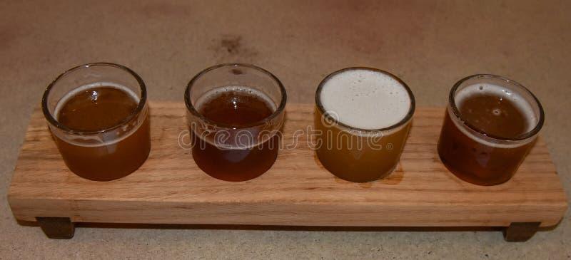 Het houten dienblad van de bierbemonstering met vier brouwt stock foto's