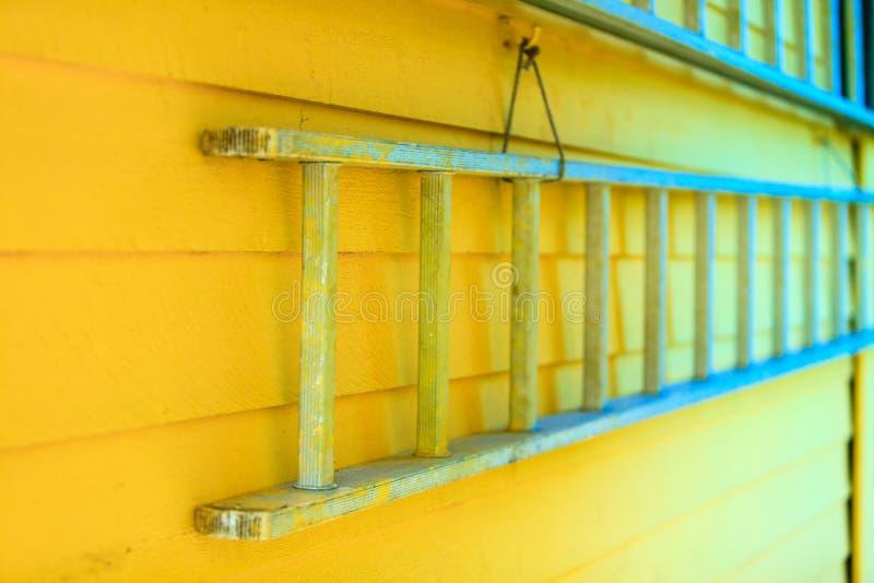 Het houten ladder hangen op gele huismuur stock foto