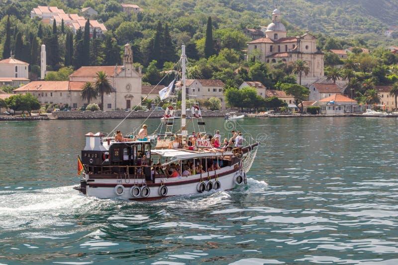 Het houten oude jacht met toeristen vaart op de baai van Boka Kotorska op de achtergrond van de stad van Prcanj stock foto's