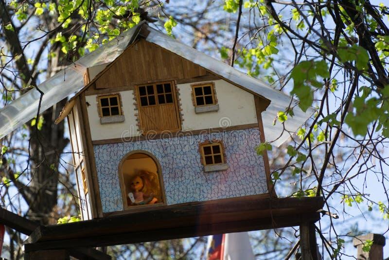 Het houten stuk speelgoed huis hangen op een boom met binnen baby - pop stock fotografie